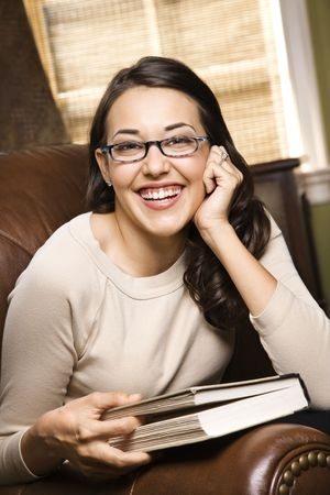 CaucasianHispanic young woman sitting in leather chair holding book and smiling at viewer. photo