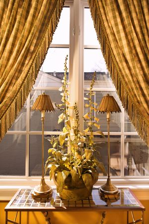 home accents: Interior view of window with curtains pulled back and decorative table with lamps and plant. Stock Photo