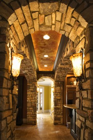 sconce: View of foyer through stone archway in affluent home. Stock Photo