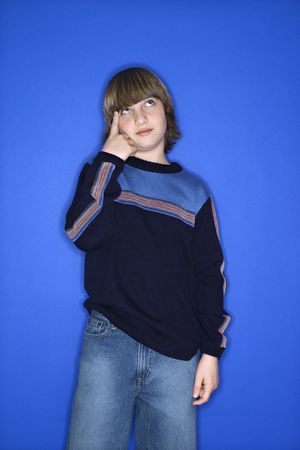 Caucasian boy with hand pointing at his head  against blue background.