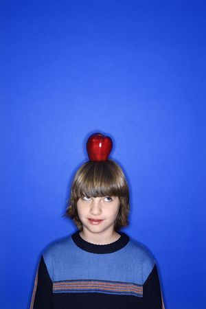 Caucasian boy with apple on his head standing against blue background. photo