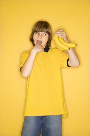 Portrait of Caucasian boy holding bunch of bananas and gesturing with finger in mouth that they are gross standing against yellow background. photo
