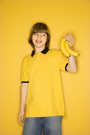 Portrait of smiling Caucasian boy holding bunch of bananas standing against yellow background. photo