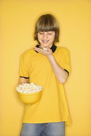Portrait of Caucasian boy smiling holding bowl of popcorn in one hand and bringing some popcorn to mouth standing against yellow background. photo