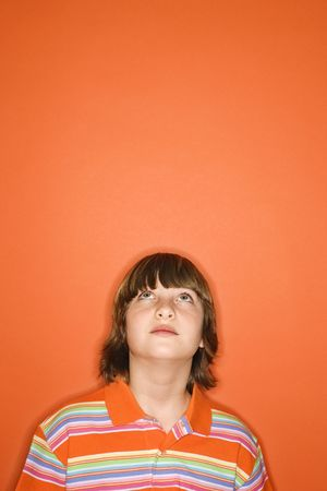 Head and shoulder portrait of Caucasian boy looking up standing against orange background. photo