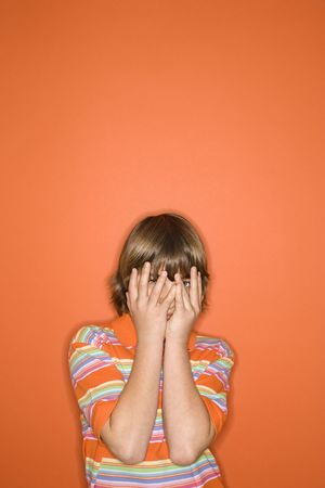 Portrait of Caucasian boy with hands covering his face standing against orange background. photo