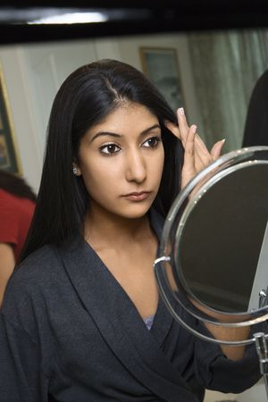 Close up of AsianIndian young woman looking in mirror primping.