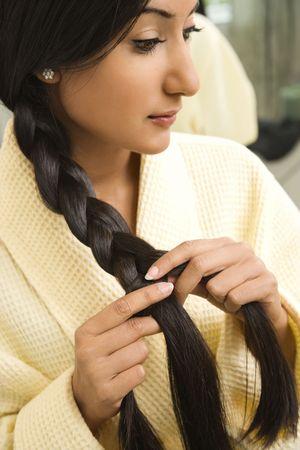 braiding: Close up profile of AsianIndian young woman braiding hair.
