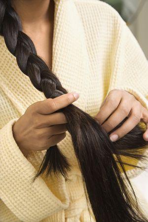 braiding: Close up of AsianIndian young woman braiding hair. Stock Photo