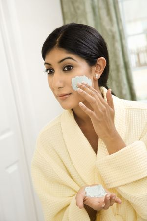 only one woman: Close up of young AsianIndian woman applying facial scrub.