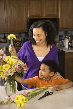 Portrait of young pregnant mother and son arranging flowers. Stock Photo - 2227056