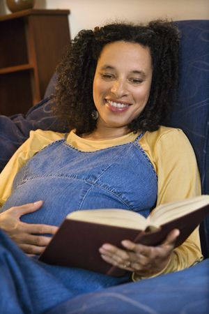 Portrait of pregnant female reading a book and holding her stomach. Stock Photo - 2227134