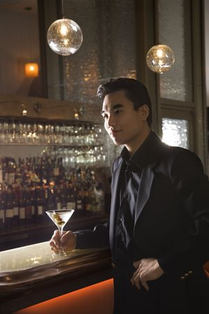 prime adult: Prime adult Asian male standing at bar with cocktail.