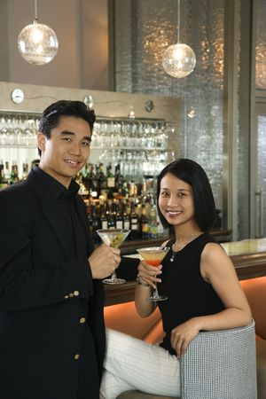 lounge bar: Prime adult Asian male and female at bar with cocktails. Stock Photo