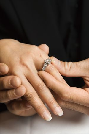 engagement ring: Prime adult Asian male putting engagement ring on females hand. Stock Photo