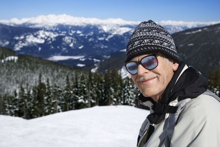 Caucasian senior man  skier in goggles posing on mountain. photo