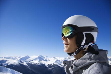 ski goggles: Caucasian teenage boy snowboarder wearing helmet and goggles on mountain.