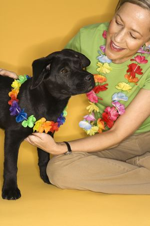 leis: Caucasian prime adult female sitting with black puppy wearing leis.
