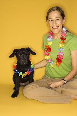 leis: Femmina principale caucasica delladulto che si siede con i leis da portare del puppy nero.