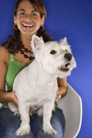 prime adult: Caucasian prime adult female holding white terrier dog.