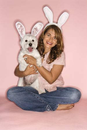 similarity: Caucasian prime adult female and white terrier dog wearing rabbit ears.