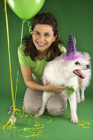 party hat: Caucasian prime adult female kneeling with fluffy white dog wearing party hat.