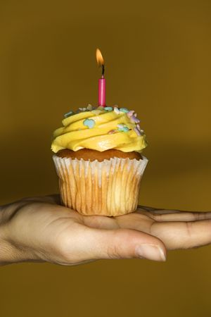 Caucasian prime adult female hand holding cupcake with lit candle. photo