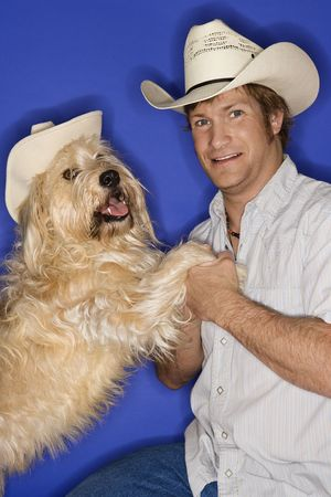 alike: Fluffy brown dog and male Caucasian young adult wearing cowboy hats.