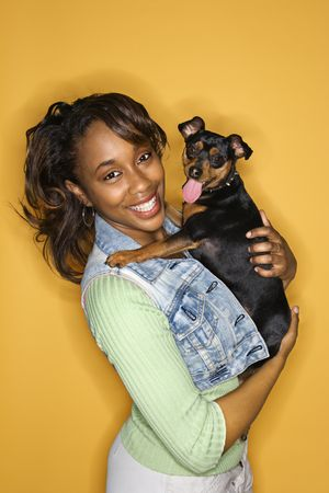 African American young adult female holding Miniature Pinscher dog. photo