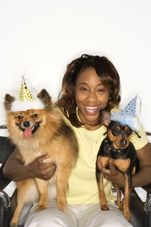 pinscher: African American young adult female holding brown Pomeranian and Miniature Pinscher dogs wearing party hats.