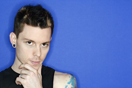 Young adult Caucasian male pierced ear and tattoo. photo