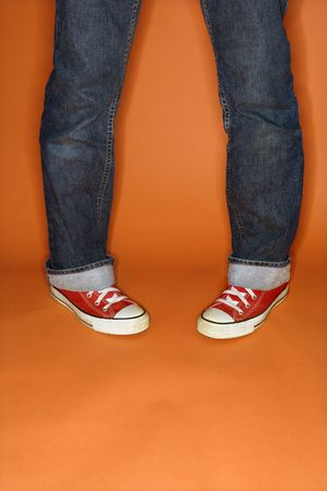 inward: Person in jeans and sneakers with feet turned inward.