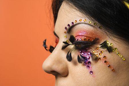 individualism: Close-up of Caucasian woman in unique makeup against orange background. Stock Photo