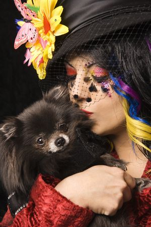 individualism: Caucasian woman in unique makeup and clothing holding and kissing black Pomeranian dog.