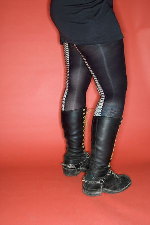 nonconformity: Portrait of womans lower body weating leggings and boots against orange background.
