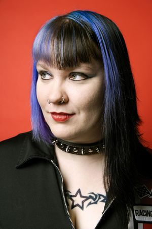 nonconformity: Woman with blue hair, tattoo, and spike collar against orange background