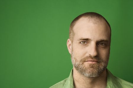 hairline: Head shot of Caucasian man with beard and receding hairline against green background.