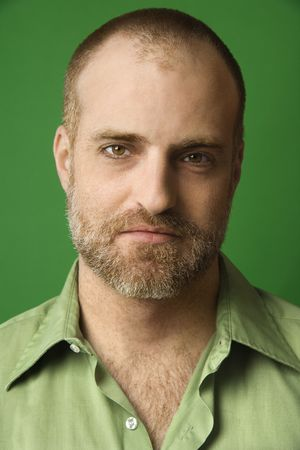 hairline: Head and shoulder portrait of Caucasian man with receding hairline and beard against green background. Stock Photo