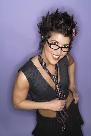 spiked hair: Caucasian Hispanic woman wearing eyeglasses smiling looking at viewer  holding necktie standing against purple background.