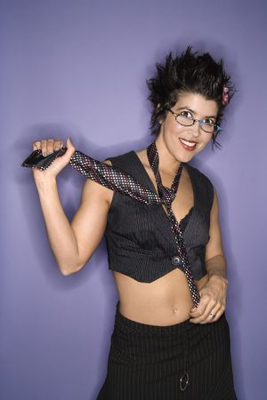 spiked hair: Portrait of smiling Hispanic woman wearing eyeglasses and necktie with exposed midriff standing against purple background.
