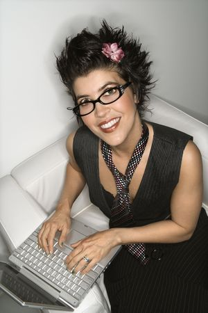 spiked hair: High angle view of Hispanic woman smiling and typing on laptop. Stock Photo