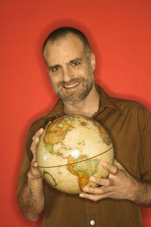 receding: Portrait of smiling Caucasian man holding globe standing against orange background.