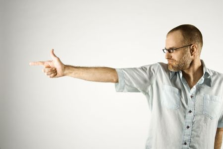 receding: Portrait of Caucasian man holding hand out like a gun standing against white background.