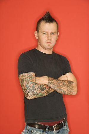 Homme de race blanche avec mohawk et tatouages debout avec les bras croisés contre le fond orange.