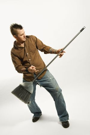 pretend: Caucasian man with mohawk playing broom like guitar against white background.