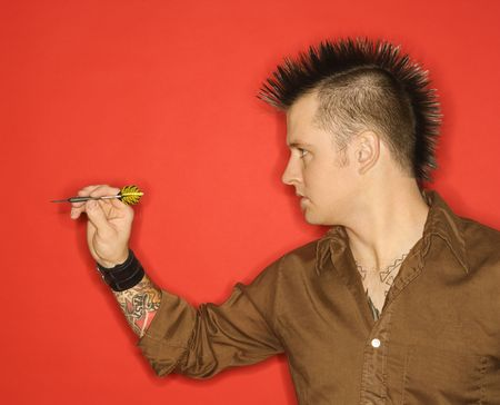 dart: Side view of Caucasian man with mohawk holding dart against red background.