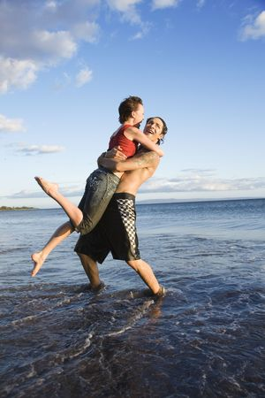 frolicking: Caucasian young adult couple frolicking on beach.