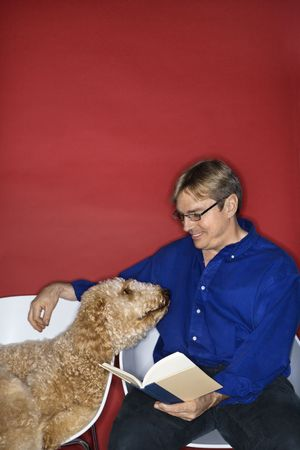 Middle-aged Caucasian man with Goldendoodle dog reading book. photo