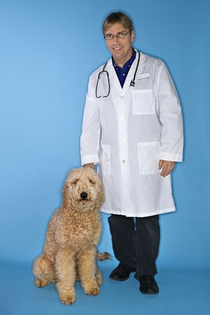 Middle-aged Caucasian male veterinarian with Goldendoodle dog. photo