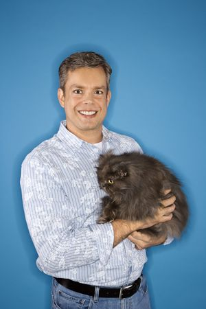 Mid-adult Caucasian man standing holding Persian cat. photo